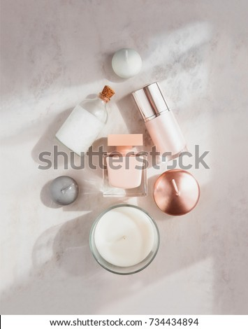 Spa beauty products flatlay in shape of Christmas tree on white marble table. Coconut oil, luxury cream, serum, perfume, candles.