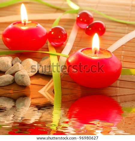spa candle and water reflection showing zen concept