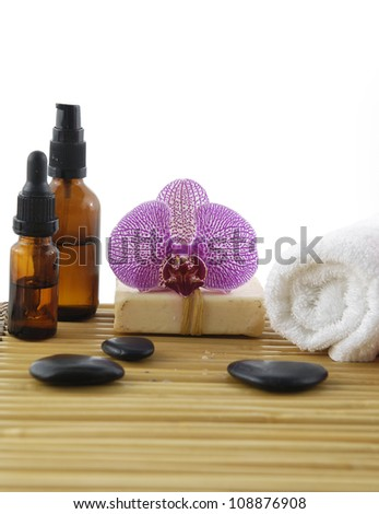 spa composition of soap, towel, soap, and massage oil on wooden boards - stock photo