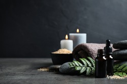 Spa composition with aroma oil on grey table, space for text