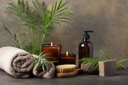 Spa composition with candles, towels, massage brush, volcanic pumice stone, care cream in dark glass bottle and green tropical plants. Beauty spa treatment and relax concept