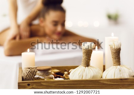 Spa composition with herbal bags and candles with blurred woman on background #1292007721