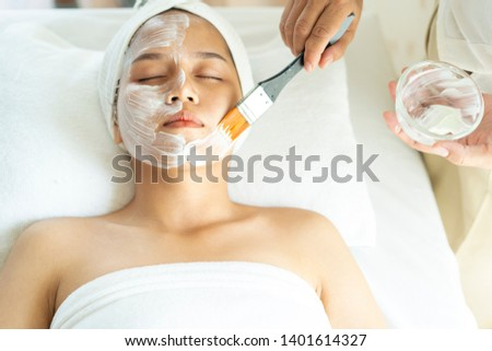 Spa concept. Asian young woman getting facial care or nutrient facial mask by beautician in beauty spa salon,Face peeling mask, spa beauty treatment, skincare.