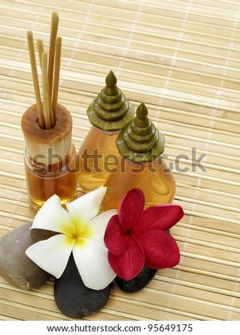 Spa Concept: bottles of essential oil, massage stones,aromatherapy incense sticks & flowers on bamboo mat