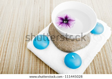 spa concept build of stone, petal flower, clean water cap and white towel  and blue candles, isolated on white background