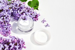 Spa concept cream in a glass jar for cream with lilac flowers and green lilac leaves on a white background. copy space.
