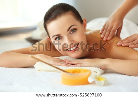 Spa concept. Hands massaging female back with scrub