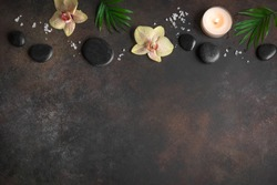 Spa concept on dark background, tripical plants, candles and zen like black stones, top view, copy space. Spa composition.