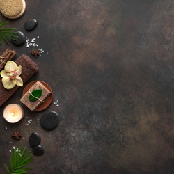 Spa concept on dark background, tripical plants, candles and zen like black stones, top view, copy space. Spa composition with natural skincare products.