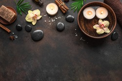 Spa concept on dark background, tripical plants, candles and zen like black stones, top view, copy space. Spa composition with natural massage products.