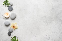 Spa concept on white stone background, palm leaves, flower, candle and zen like grey stones, top view, copy space.