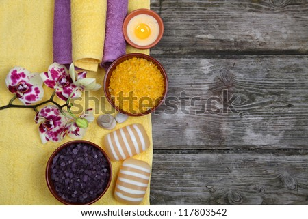 Spa concept: soap, salt for baths, a flower and towels on a wooden background