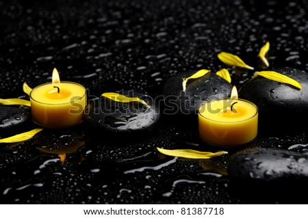 Spa concept-two candle with yellow flower petals on pebbles