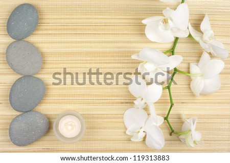 SPA concept: white orchids, candles and stones on mat.