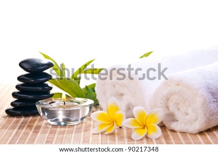 Spa concept with black zen stones, flowers on bamboo mat background