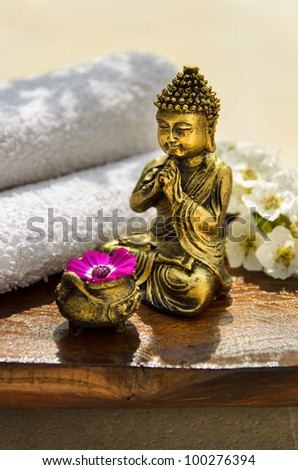 Spa concept with Buddha, towels, flowers and wood.