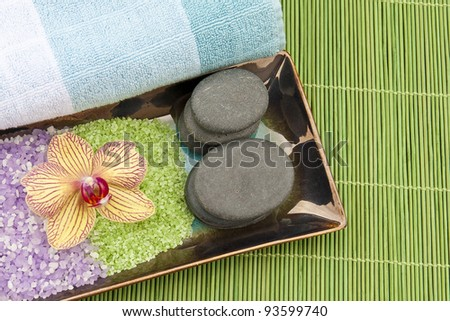Spa concept with mineral bath salt, massage stones, towel and orchid on green bamboo background