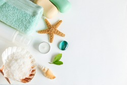 Spa cosmetics and towel with sea stars and salt in the scallop shell on a white background on top