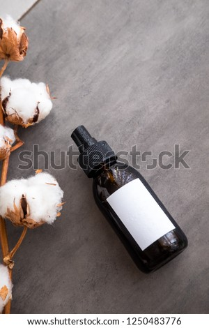 Spa cosmetics in brown glass bottles with white label on dark gray concrete table, flatlay. Copyspace for text. Beauty blogger, salon therapy, branding mockup, minimalism concept. Vertical #1250483776