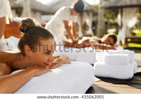 Spa Couple Massage. Beautiful Happy Smiling Woman And Healthy Man Enjoying Relaxing Body Massage Treatment Outdoors At Beauty Salon. People At Romantic Day Spa Resort. Health Care And Relax Concept