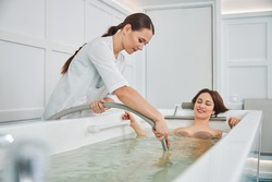 Spa employee in white outfit holding plastic pipe and getting it in whirlpool tub for massaging relaxed client with water