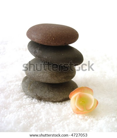 Spa essentials (pyramid of stones with white towel and flower) - stock photo