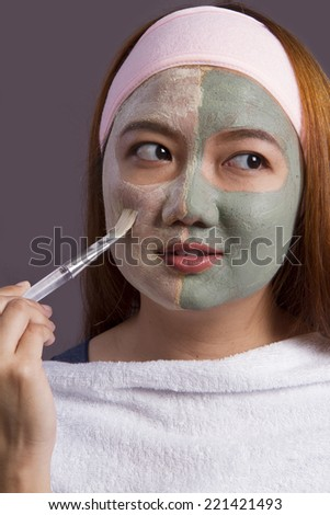 Spa face mask.teen girl applying facial clay mask. Beauty treatments.