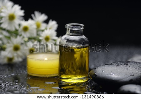 Spa feeling with candle , bouquet of daisies, massage oil, pebbles