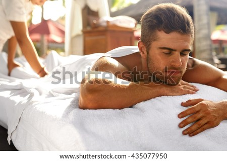 Spa For Man. Beautiful Healthy Happy Male Model Relaxing At Day Spa Beauty Salon. Handsome Guy Enjoying Summer Body Relaxation Treatment, Lying On Relax Massage Table Outdoors. Health Care Concept