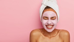Spa girl with pleased facial expression, applies clay mask on face, gets beauty treatments, wears white soft towel on head, stands with bare shoulders, isolated over pink wall with copy space area