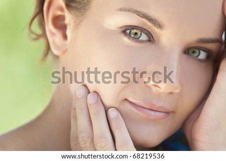 Spa Health and beauty portrait of a beautiful brunette young woman with stunning green eyes, shot outside in natural light