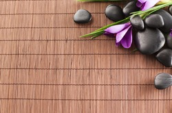 spa, heath and beauty concept - massage stones with flowers on mat