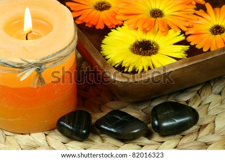 Spa in orange color: candle, calendula flowers and pebbles - stock photo