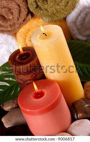 Spa like feeling including candles, leaves, rocks and towels