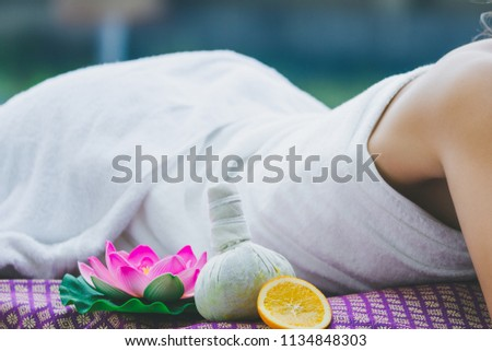 Spa massage concept, Close up of spa setting with young asian woman Getting traditional spa treatments in pool spa resort, Thailand