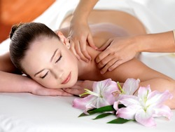 Spa massage on a shoulder for young beautiful woman in  beauty salon - indoors