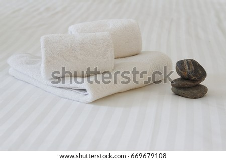 Spa, massage, travel and vacation concept. Freshly folded towel on a white linen bed with a stack of stones.  #669679108