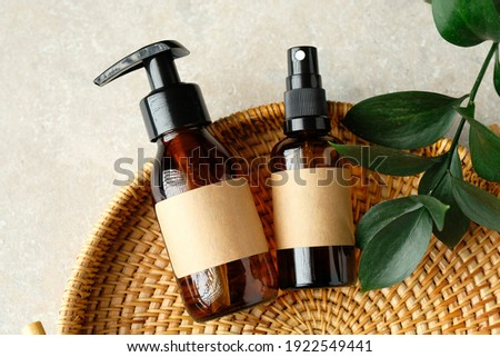 SPA natural organic cosmetics for personal hygiene. Amber glass pump and spray cosmetic bottles, green leaf in rattan container in bathroom. Сток-фото ©