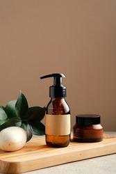 SPA natural organic cosmetics set on wooden board. Shower gel or shampoo amber glass dispenser bottle, jar of moisturizer cream, homemade soap, green leaf. Bath beauty product packaging design