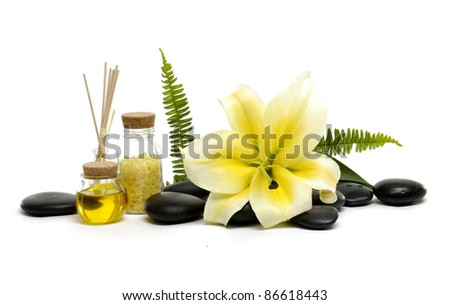 spa objects and flower madona lily and spa stones with bottle of essential oil
