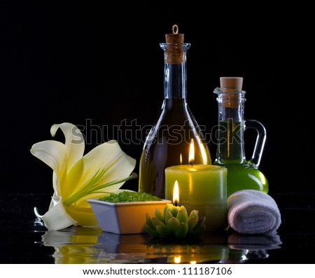 Spa oil, candles, flowers and treatment cosmetics on black background