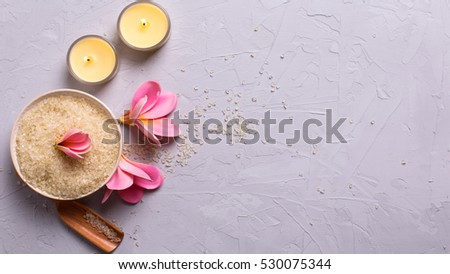Spa or wellness setting in yellow color. Sea salt in bowl, candles and flowers on grey textured background. Selective focus. Place for text. Flat lay. #530075344