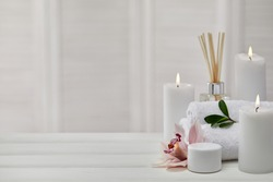 Spa products with aromatic candles, orchid flower and towel on white wooden table. Beauty spa treatment and relax concept. copy space