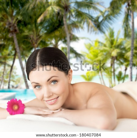 spa, resort and vacation concept - smiling woman in spa salon lying on the massage desk