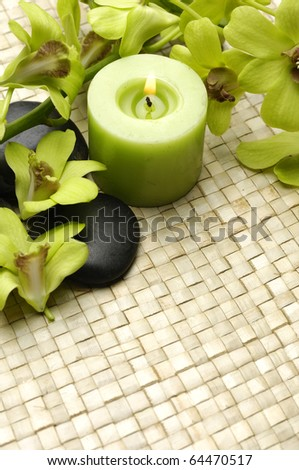 Spa resort composition - burning candles, orchid flowers and zen stones on straw mat