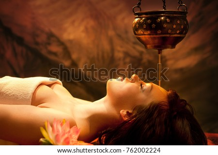 Spa salon: Beautiful Young Woman having Shirodhara - Ayurveda Oil Massage in India Spa Salon with Lotus