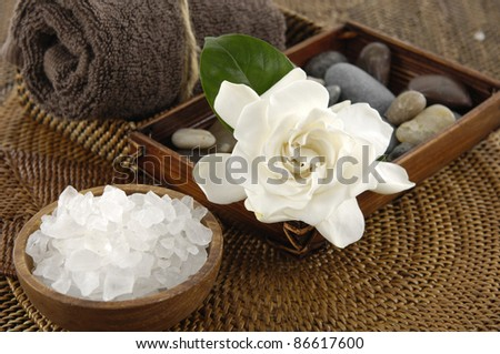 spa salt in bowl and gardenia flower and stones on burlap texture