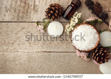 Spa, sauna and wellness setting with sea salt, oil essence, cones and candle on wooden background. Fall autumn wellness concept, Relax and treatment therapy. Close up