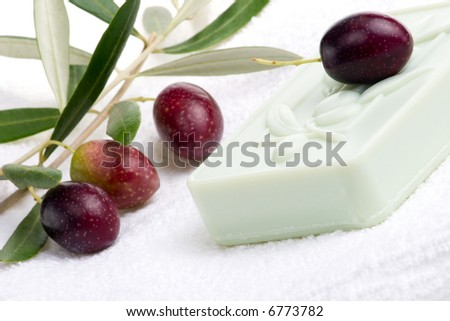 Spa set - fresh black olives, oils, organic soap and towels over white towel. best suited for relaxing and health commercials