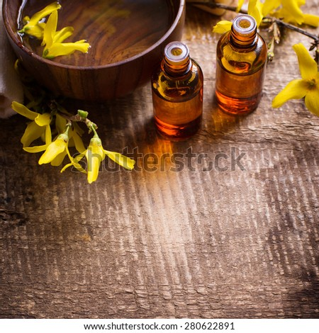 Spa setting. Essential aroma oil in bottles , water in bowl, yellow flowers on aged wooden background. Selective focus. Place for text.  Square image.